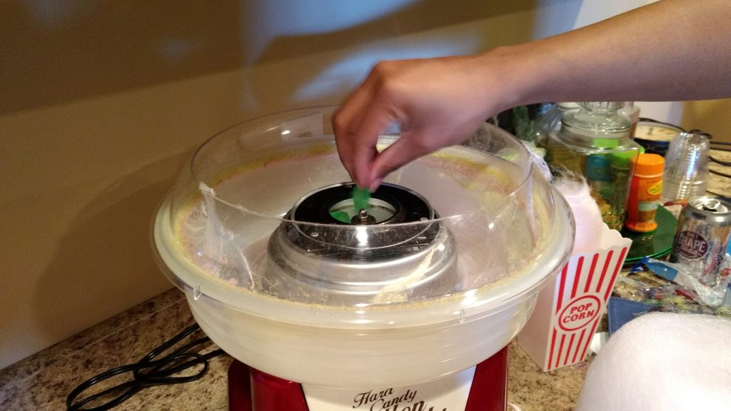 Dropping candy into cotton candy machine